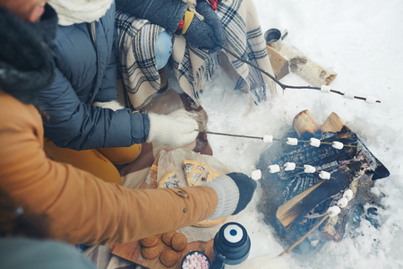 Directly above view of unrecognizable winter campers sitting by fire and roasting marshmallows on stick in winter Stock fotó