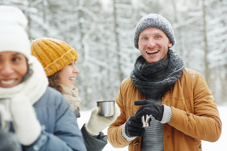 Cheerful excited young friends in warm clothing standing in winter forest and drinking hot tea to get warm while chatting together during hiking