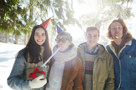 Group of four young people celebrating Christmas outdoors in beautiful forest, all wearing party caps Stock fotó
