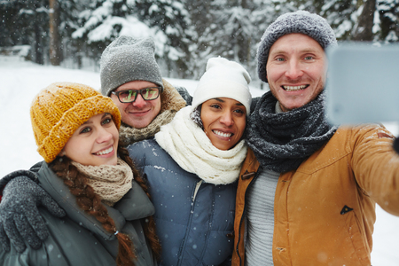 Positive excited young friends in warm hats and scarves posing for selfie and embracing in winter park Stockfoto - 110665224
