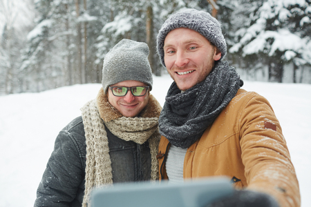 Positive handsome young men in hats and scarves standing in winter forest and making self-portrait on smartphone
