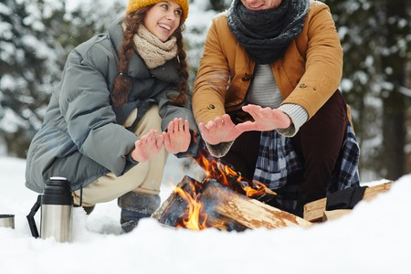 Close-up of travelers in puffy jackets sitting by campfire and warming hands at winter camping