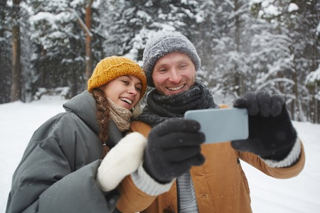Jolly excited beautiful young couple in warm clothing standing in winter forest and smiling while taking selfie ion smartphone