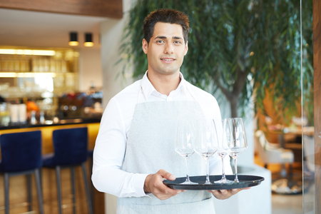 Portrait of young waiter in uniform holding tray with empty wineglasses standing at restaurant