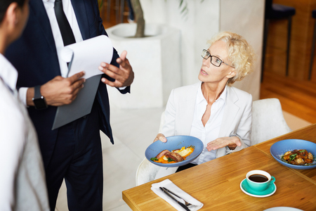 Femme mûre assise à la table pendant le déjeuner d'affaires et se plaignant de la nourriture au propriétaire du restaurant Banque d'images