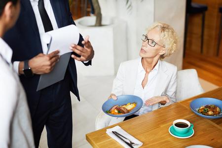 Mujer madura sentada a la mesa durante el almuerzo de negocios y quejándose de la comida al dueño del restaurante Foto de archivo