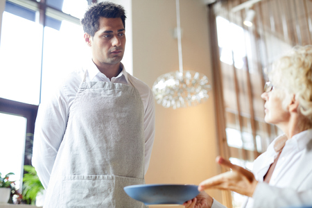 Young waiter standing and listening to the client who is dissatisfied with the dish