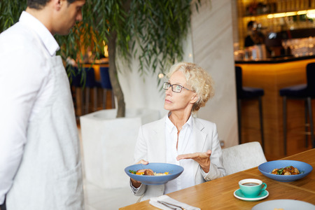 Displeased mature businesswoman conflicting with waiter because of poor quality of dish in restaurant