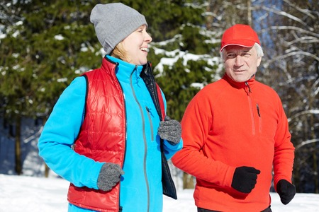 Happy mature sporty couple in activewear jogging in winter forest in the morning