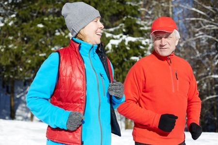 Heureux couple sportif mature en vêtements de sport jogging dans la forêt d'hiver le matin Banque d'images