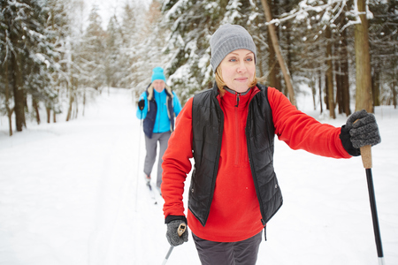 Mature sportswoman and her husband in active wear skiing in snow in winter forest 免版税图像