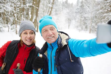 Esquiadores felices en ropa activa haciendo selfie durante su entrenamiento en el bosque de invierno