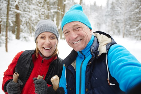 Cheerful mature couple in winter sportswear looking at you during their training on skis Stok Fotoğraf