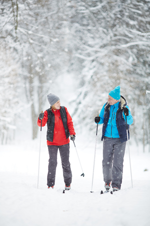 Sporty mature spouses in active wear skiing in snowfall at leisure on winter day