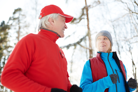 Mature woman in active wear talking to her husband while both running outdoors in the morning