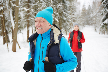 Mature man in blue active wear looking forwards while searching for place for skiing practice Imagens