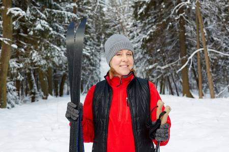 Happy mature female in active wear standing in winter forest after skiing training 免版税图像