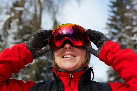 Smiling active mature female in sportswear, gloves and skiing goggles training in winter forest 스톡 콘텐츠