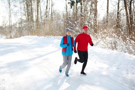 Mature spouses in winter sportswear jogging down snow road on sunny day in the forest 版權商用圖片