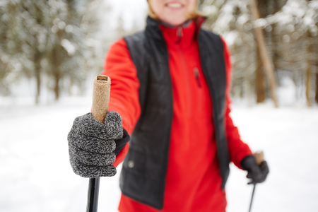 Gloved hand of active woman holding stick while skiing or trekking in winter forest or park 스톡 콘텐츠 - 110665036