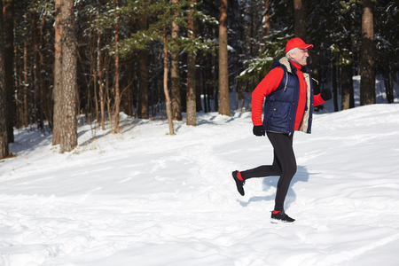 Side view of happy active mature man jogging in winter forest among evergreen trees 스톡 콘텐츠