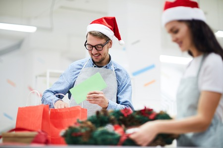 Cheerful positive young man in Santa hat wearing apron and eyeglasses standing at table and putting Christmas card in red paper bag while packaging holiday gifts in workshop