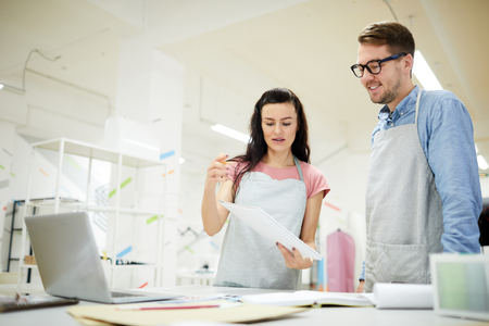 Content confident attractive lady in apron showing sketch and explaining idea of fashion design to colleague while they working in tailoring studio Stock Photo