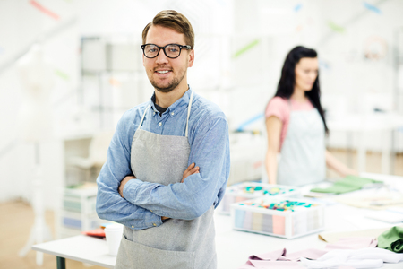 Cheerful confident young male tailor in apron and glasses crossing arms on chest and leaning on table while looking at camera in own atelier
