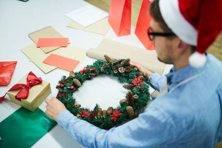 Busy young man standing at table with gift box and colorful papers and decorating Christmas wreath in modern workshop