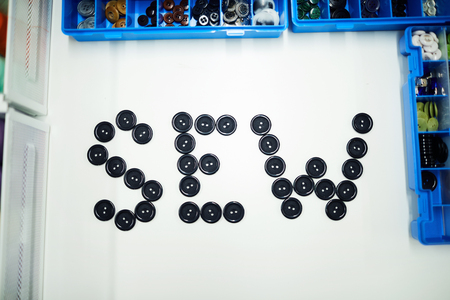 Top view of SEW word made of black buttons on table in tailoring studio, background shot