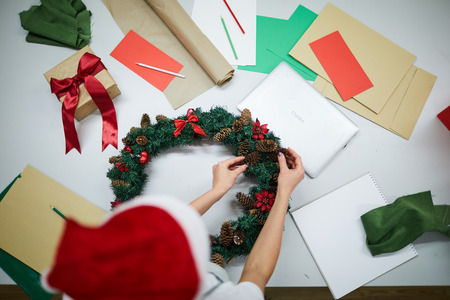 Directly above view of unrecognizable craftsperson in Santa hat standing at desk with papers and laptop and decorating Christmas wreath with pine cones Stock Photo
