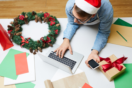 Top view of young man in Santa hat and eyeglasses leaning on table with colorful papers and browsing internet on laptop while searching for information in office