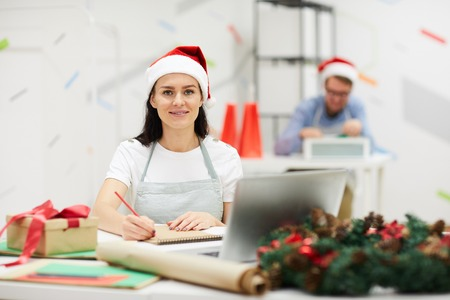 Smiling pretty young lady in Santa hat sitting at table and drawing in sketchpad while creating Christmas design in modern workshop, she looking at camera