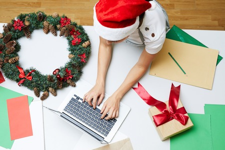 High angle view of busy woman in Santa hat leaning on big table with Christmas decorations and typing on laptop in workshop Stock Photo