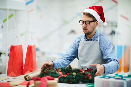 Serious concentrated young real elf in Santa hat and glasses wearing apron standing at table and making Christmas wreath in workshop