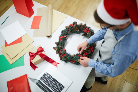 High angle view of busy man in apron and Santa hat standing at desk with colorful paper sheets, gift box and laptop and working on Christmas wreath in workshop
