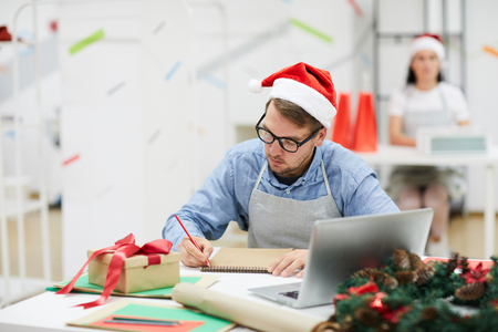 Serious concentrated young male designer in Santa hat sitting at table with laptop and gift box and planning work in creative studio Stockfoto - 110926587
