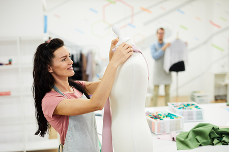 Happy beautiful young female tailor with black hair enjoying her work in atelier full of light, she wrapping mannequin in fabric while elaborating design of garment
