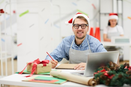 Happy handsome creative designer with beard wearing Santa hat and glasses sitting at messy table and smiling at camera in office, he making sketch Stock Photo