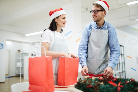 Cheerful positive young employees in Santa hats and aprons standing at table and packaging Christmas presents, they working in modern office