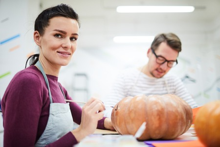 Cheerful confident brunette young lady in apron sitting at table and painting pumpkin in art studio full of light
