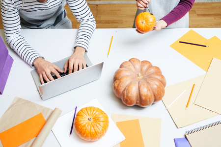 Unrecognizable busy designers working in art studio: woman painting Halloween pumpkin while man typing on laptop Stock Photo