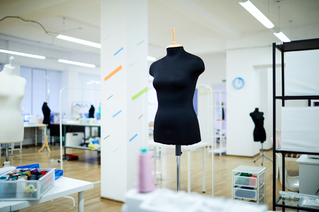 Black mannequin on metal bar place in large tailoring workshop with good illumination and colorful design on walls