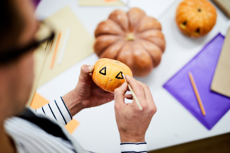 Close-up of unrecognizable man painting eyes on pumpkin with paintbrush using black color, he working in crafting studio Stock Photo