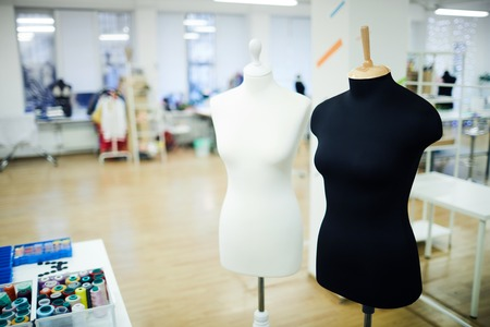Black and white mannequins placed in spacious fashion studio: threads in containers on table Stock Photo