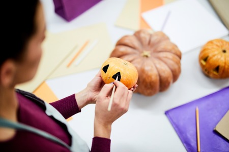 Close-up of busy craftswoman painting on small pumpkin while making spooky pumpkin in art workshop