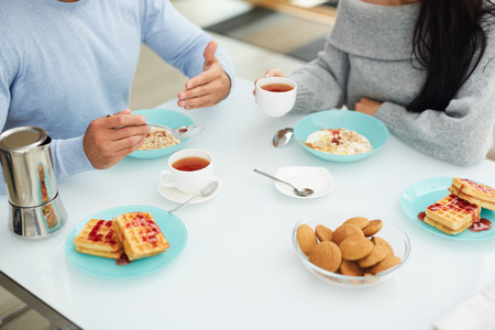 Tasty breakfast with lover: close-up of unrecognizable couple sitting at dining table and eating porridge and drinking tea while discussing interesting topic, Belgium waffles and cookies on table Reklamní fotografie - 110926810