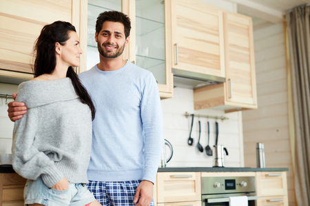 Cheerful handsome young bearded man in pajamas smiling at camera and hugging his girlfriend while they standing in cozy kitchen with wooden set