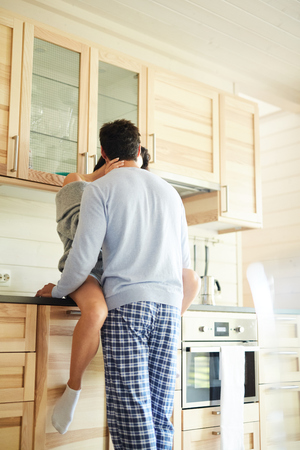 Passionate young couple kissing in modern kitchen: woman sitting on kitchen set while her boyfriend hugging her and kissing  sensually 写真素材