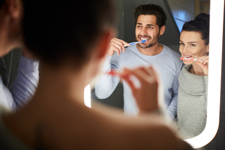 Cheerful young couple in homewear looking into mirror and having fun while brushing teeth together in bathroom